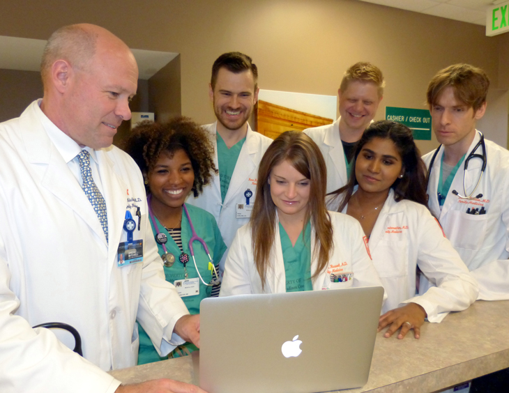 7 doctors and nurses looking down at laptop