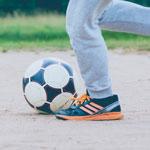 kid kicking a soccer ball